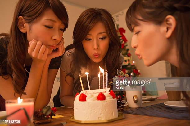 Three Young Women Blowing Out Candles on Christmas Cake