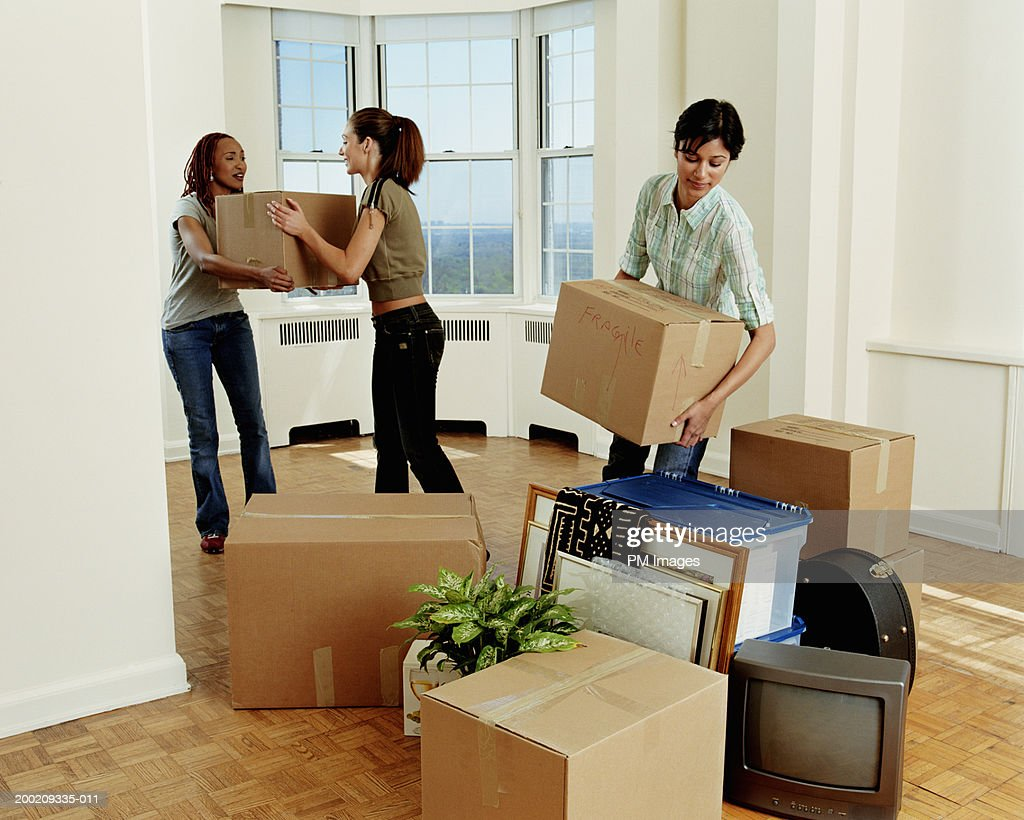 Three young women carrying boxes in apartment : Stock Photo
