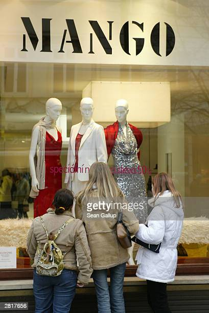 Three young women check out the display window of a Mango clothing store December 17 2003 in Prague Czech Republic Retailers throughout Europe depend...