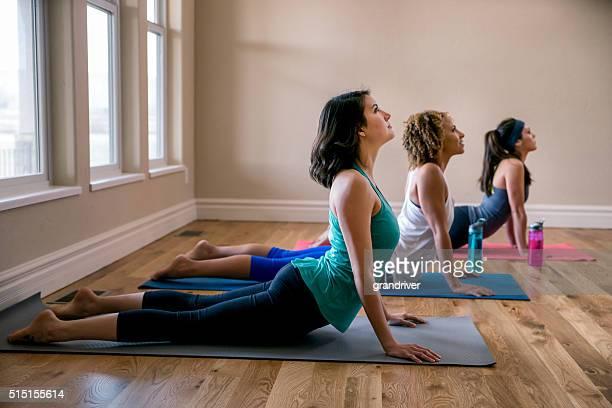 Three Young Women Doing Yoga Cobra Pose