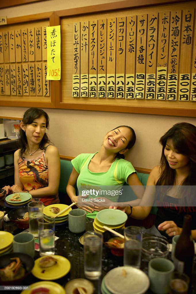 Three young women finishing meal at restaurant : Stock Photo