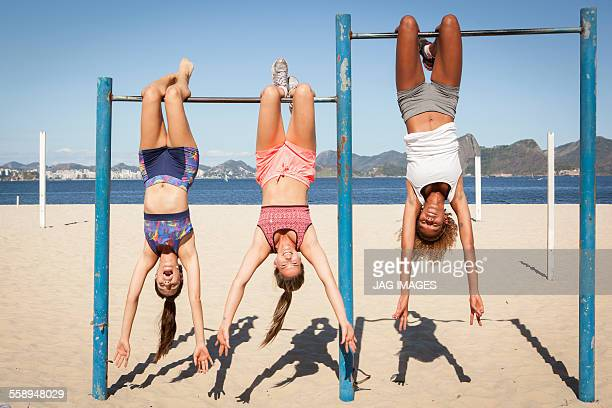 Three young women hanging upside down from bar on beach