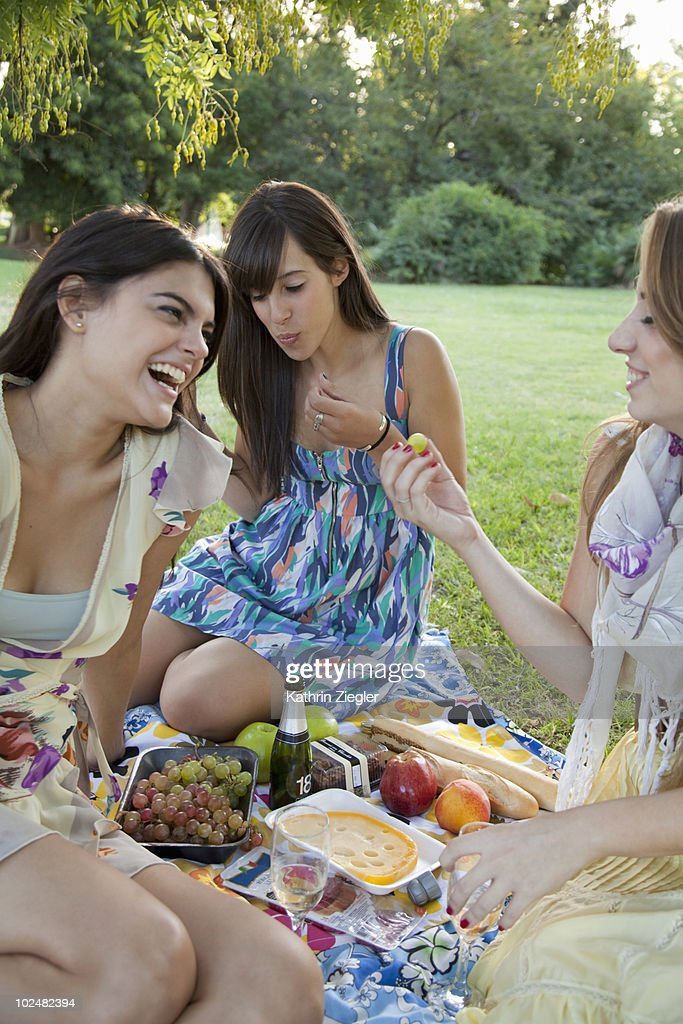 three young women having a picnic in the park : Stock Photo