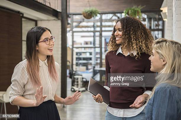 Three young women having conversation and laughing
