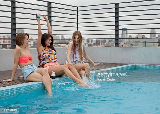 three young women having fun at the pool