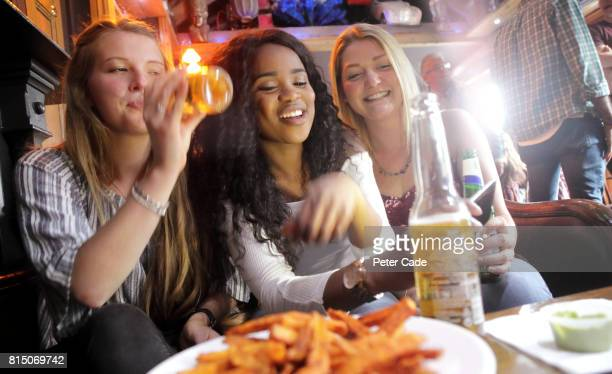 Three young women in bar, eating and drinking