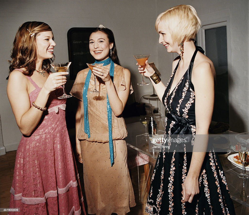 Three Young Women in Evening Dresses Stand by a Table at a Dinner Party Holding Cocktails and Talking