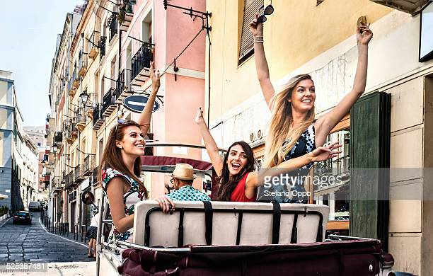 Three young women in open back seat of Italian taxi, Cagliari, Sardinia, Italy