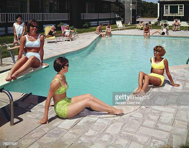 Three young women in twopiece bathing suits sit by the swimming pool in the courtyard of the Surfcomber Motel Bass River Massachusetts 1960s Several...
