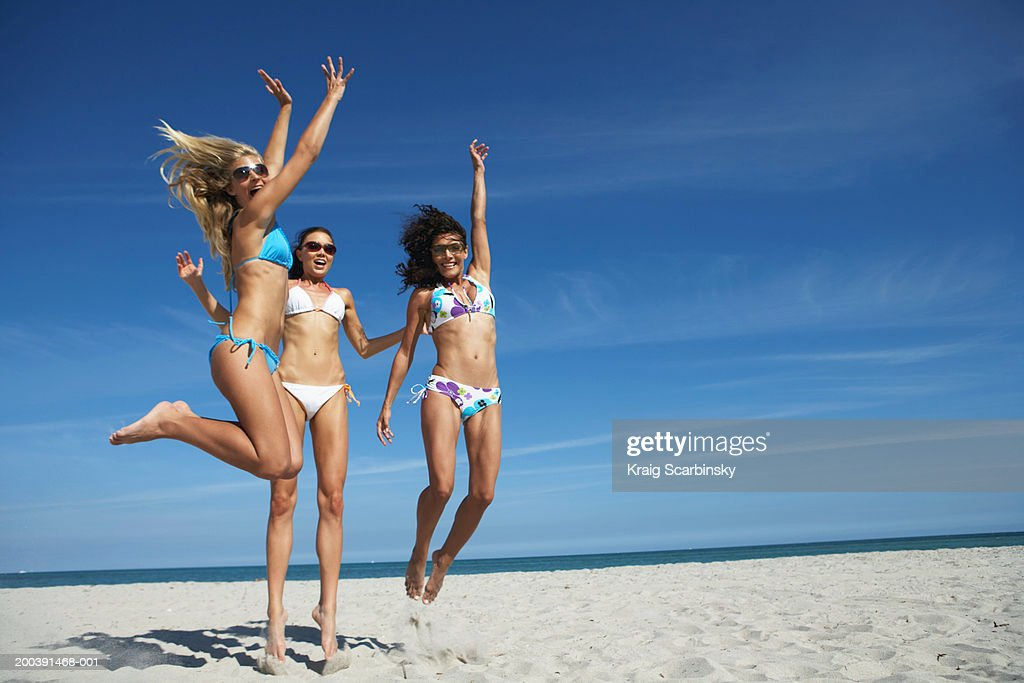 Three young women jumping on beach, portrait : Stock Photo