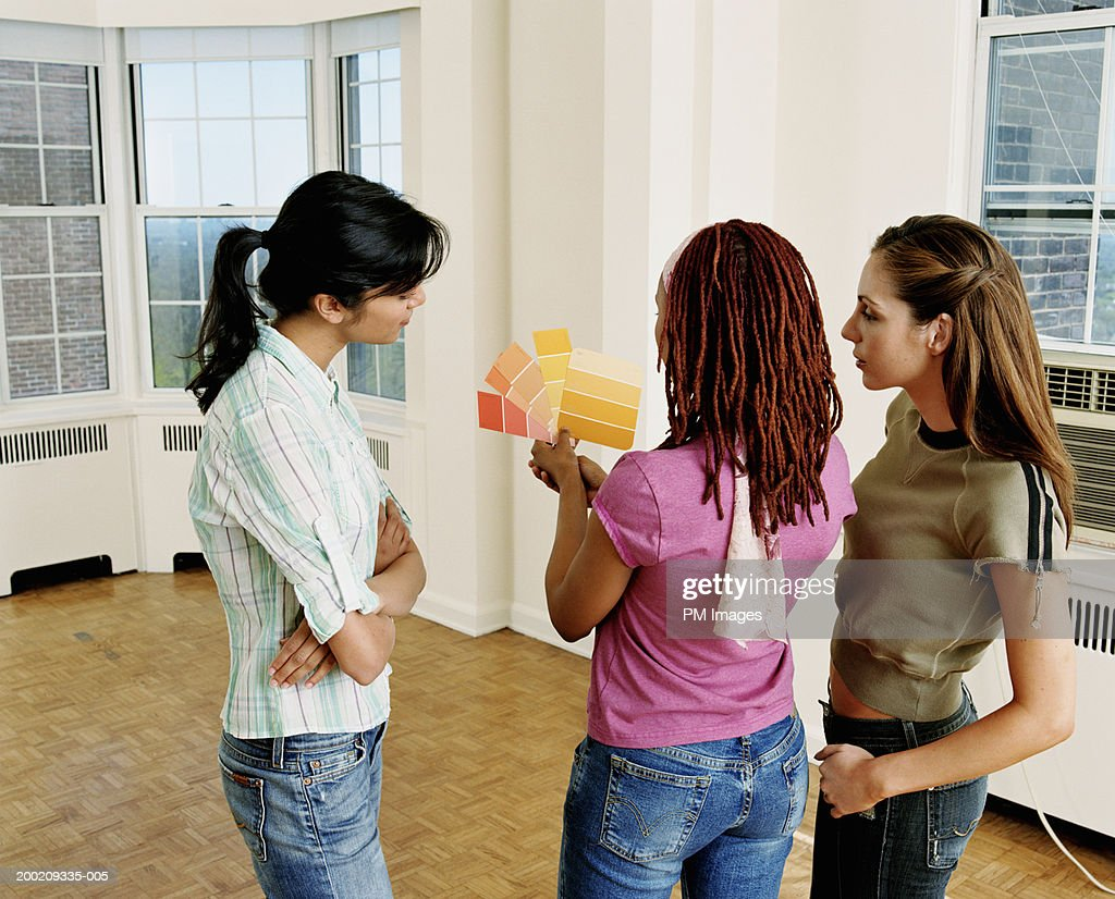 Three young women looking at color samples in empty apartment : Stock Photo