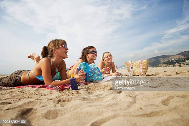 Three young women lying on beach, smiling