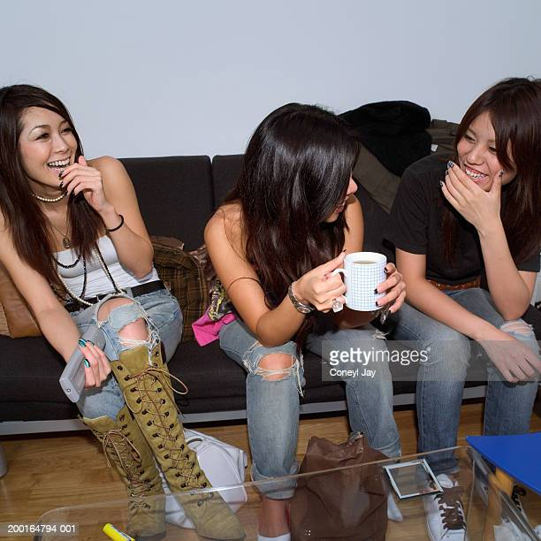 Three young women on sofa, laughing