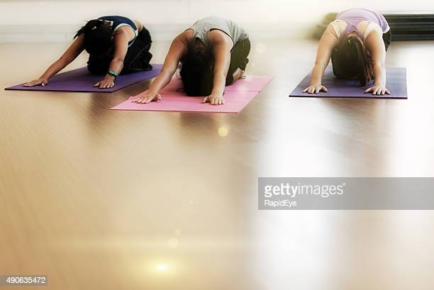 Three young women performing yoga Salute to the Sun