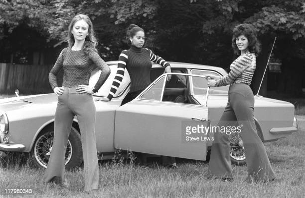 Three young women pose against a car in London's East End circa 1970