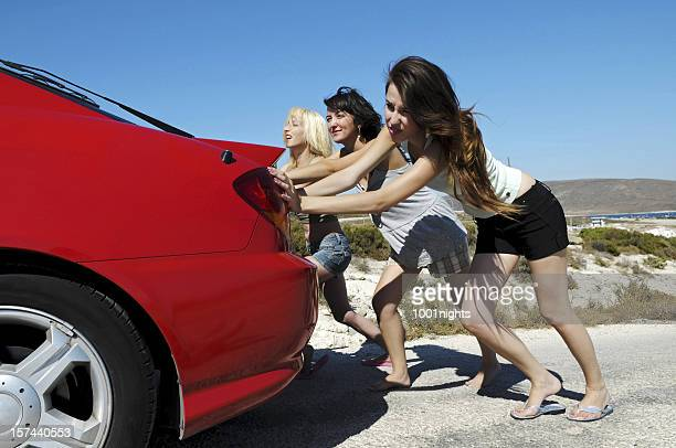 Three Young Women Pushing Red Car Along Road