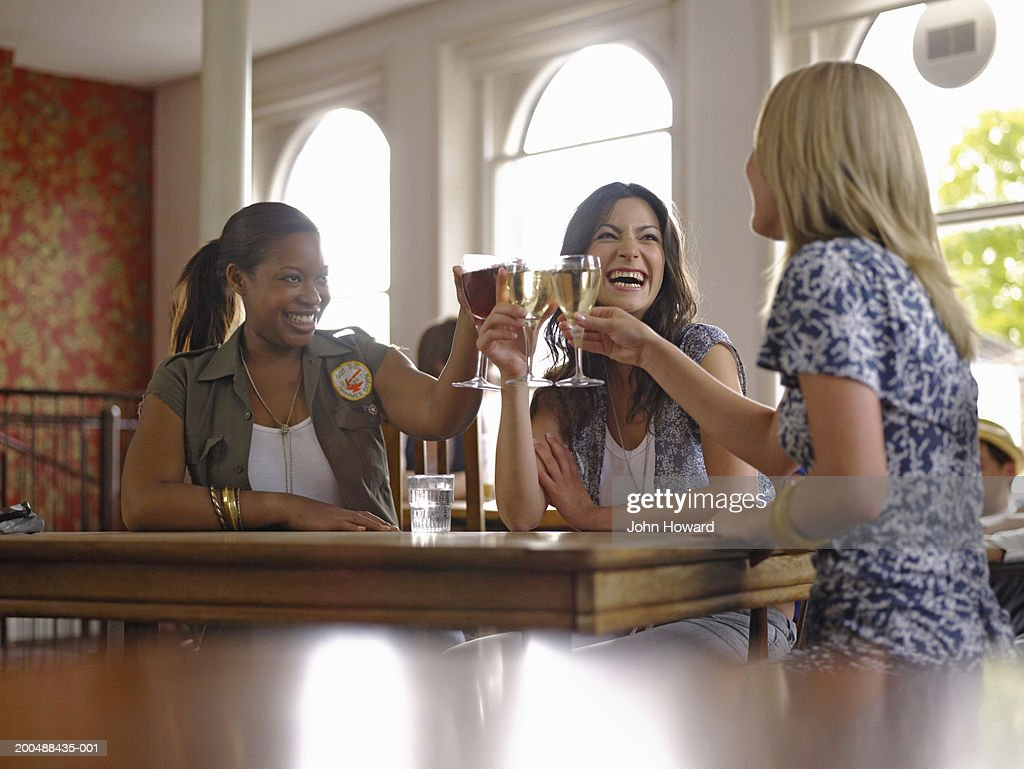 Three young women raising glasses in bar, smiling and laughing