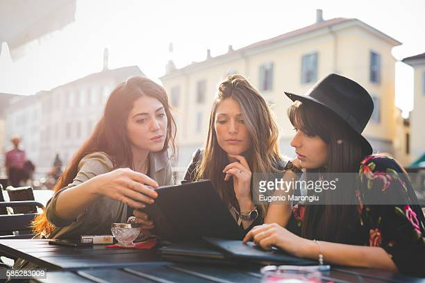 Three young women reading update on digital tablet at sidewalk cafe
