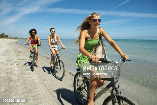 Three young women riding bicycles on beach, smiling : Stock Photo