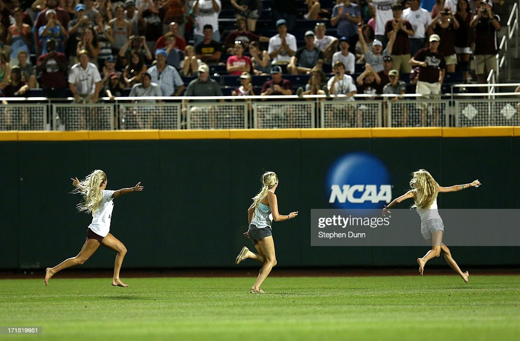 Three young women run on the field during the eighth inning as the UCLA Bruins play the Mississippi State Bulldogs during game two of the College World Series Finals on June 25, 2013 at TD Ameritrade Park in Omaha, Nebraska. UCLA won 8-0 to take the series two games to none and win the College World Series Championship.