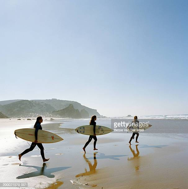 Three young women ruuning towards sea with surfboards