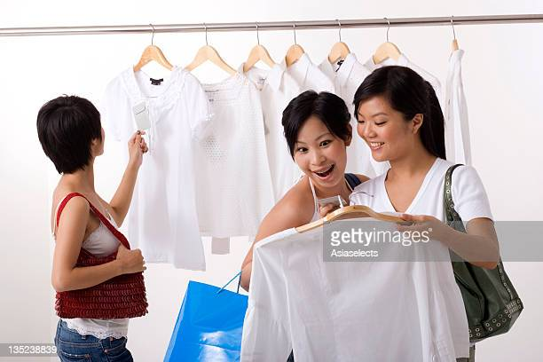 Three young women selecting dresses in a clothing store