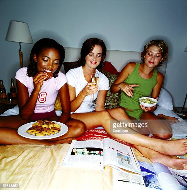 Three young women sitting on a bed eating food