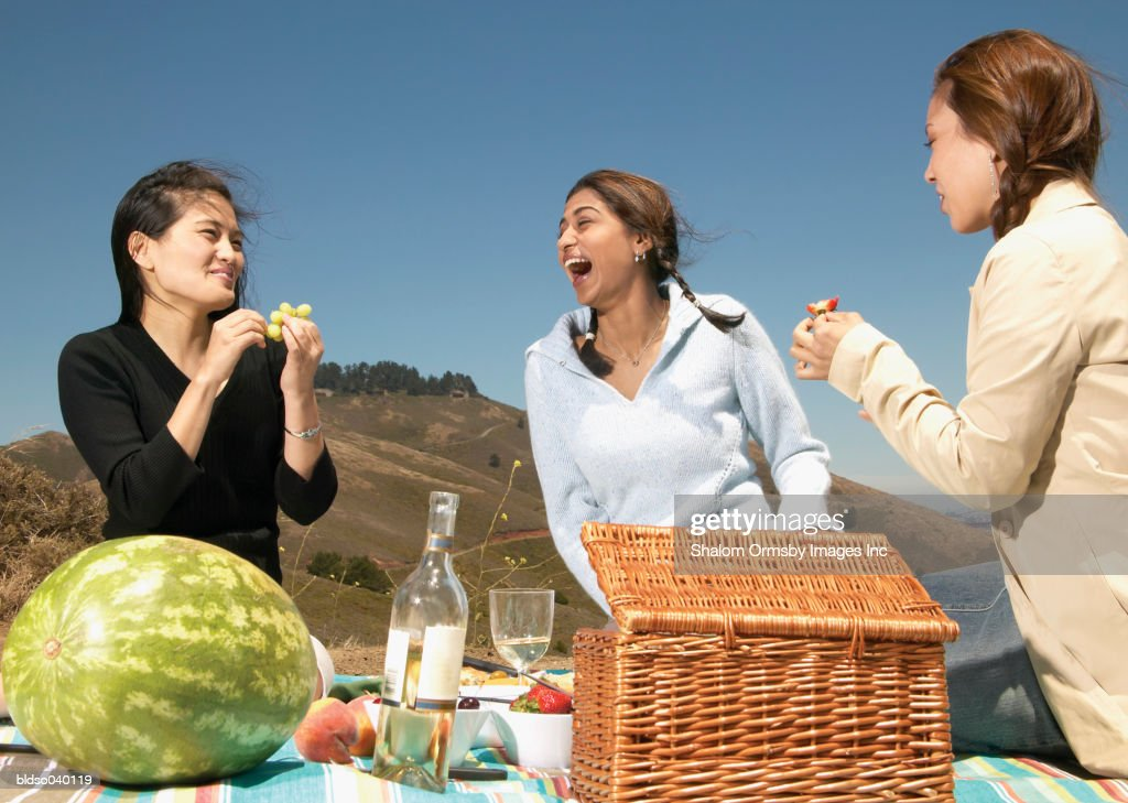 Three young women sitting together outdoors at a picnic