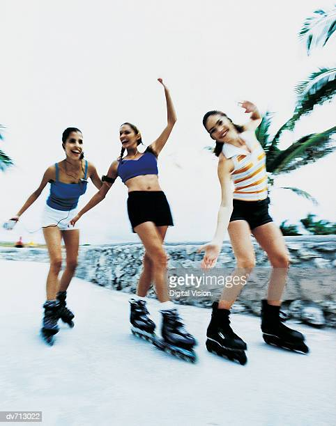 Three Young Women Skating Though a Park