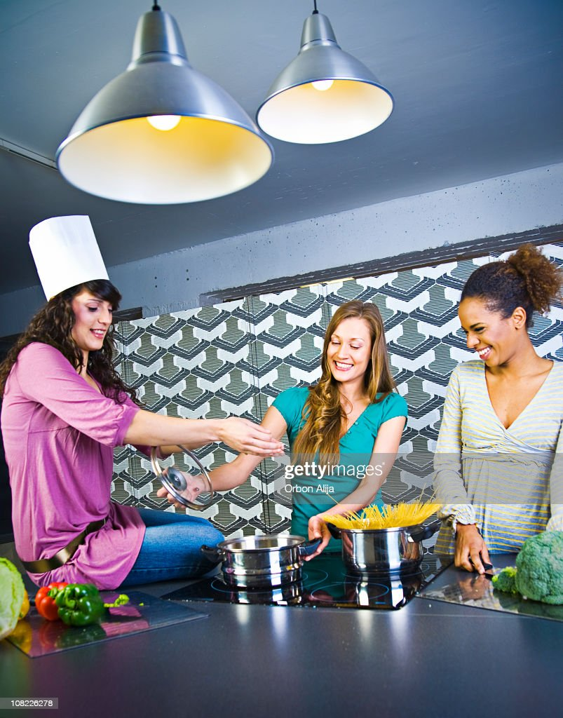 Three Young Women Smiling and Standing Around Stove Making Dinner : Stock Photo