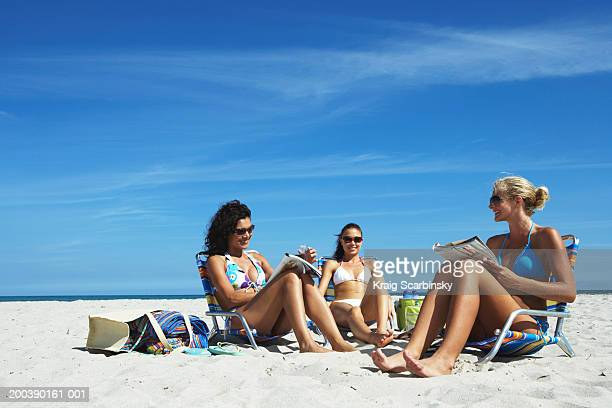 Three young women smiling on beach
