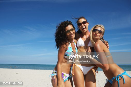 Three young women smiling on beach, portrait, close-up : Stock Photo