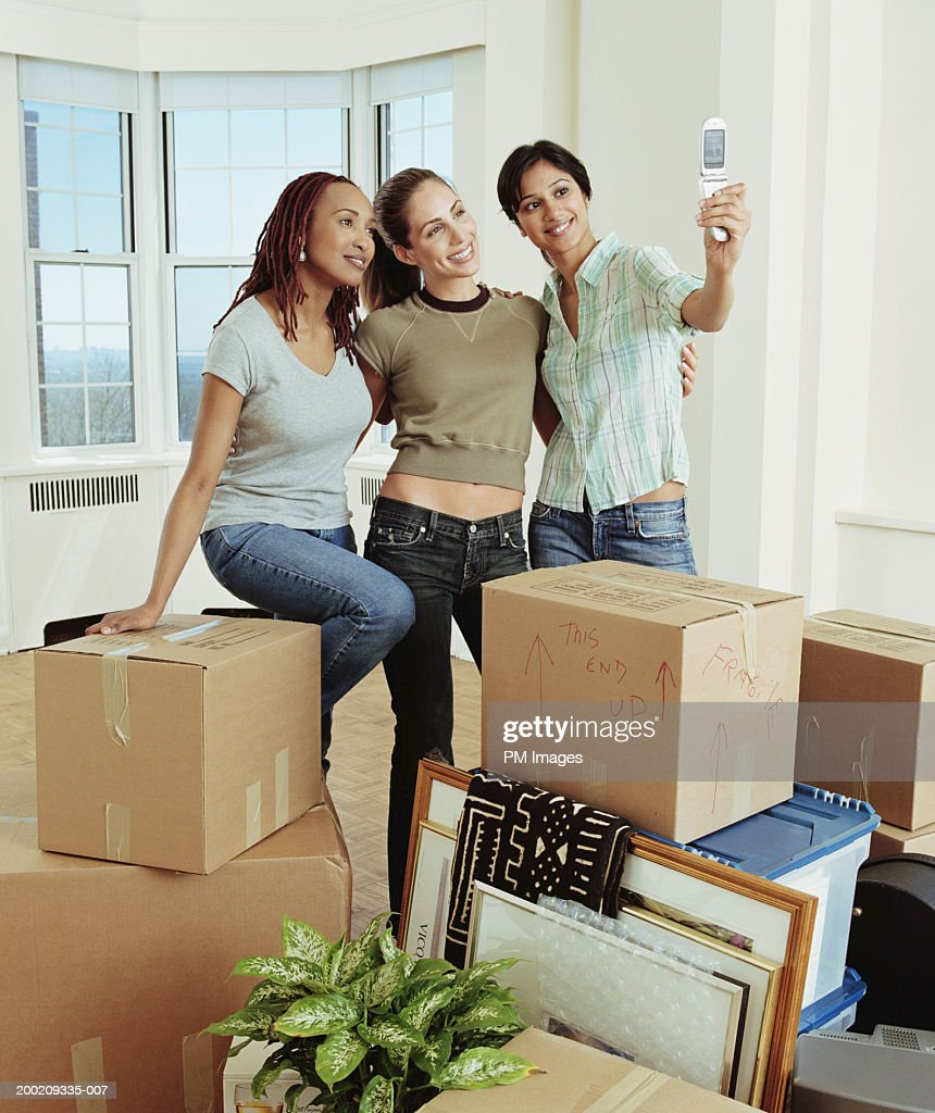 Three young women taking picture with camera phone : Stock Photo