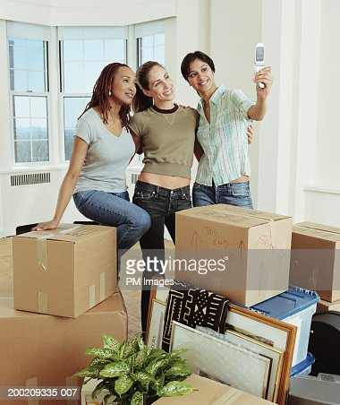 Three young women taking picture with camera phone : Photo