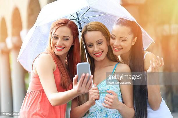 Selfie von drei jungen Frauen unter dem Regen