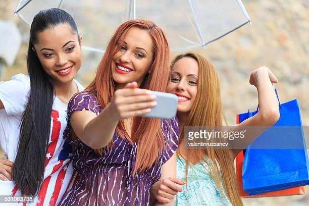 Three young women taking selfie under the rain