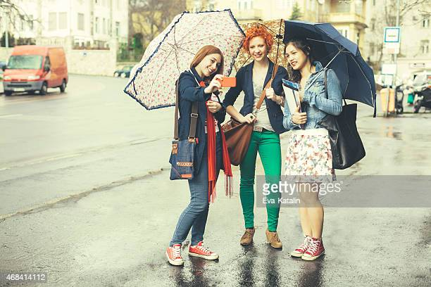 Three young women taking selfies on a rainy day