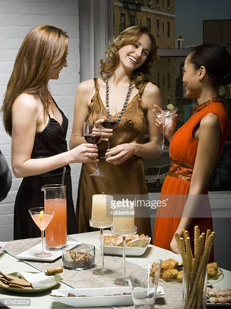 Three young women talking at a party
