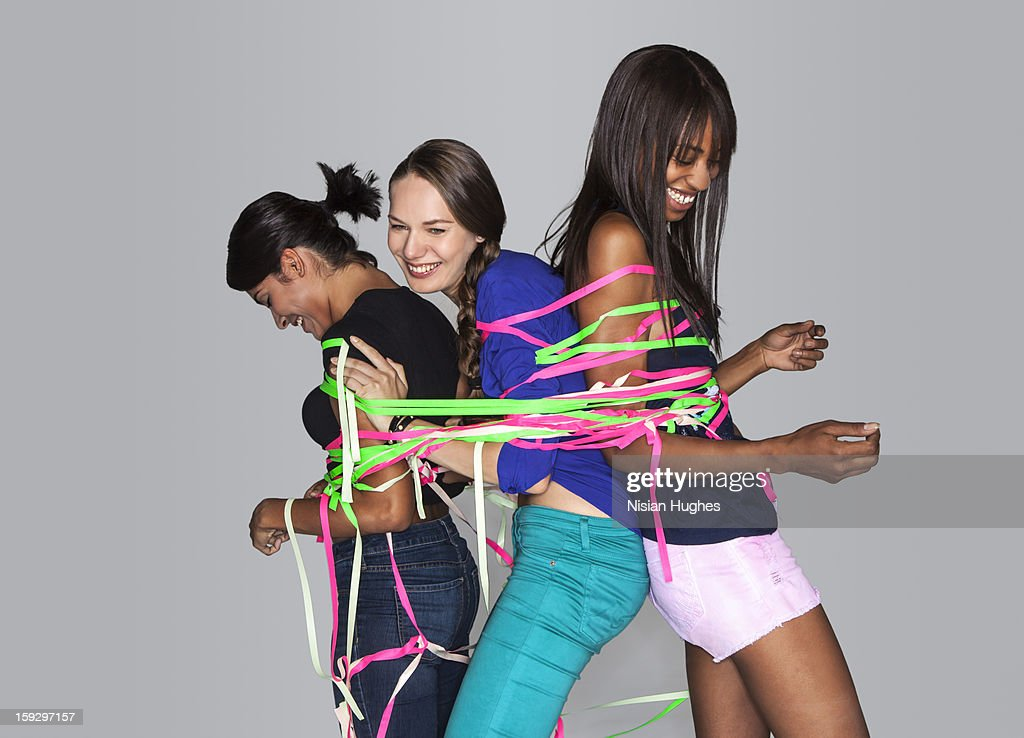 Three young women tied together : Stock Photo