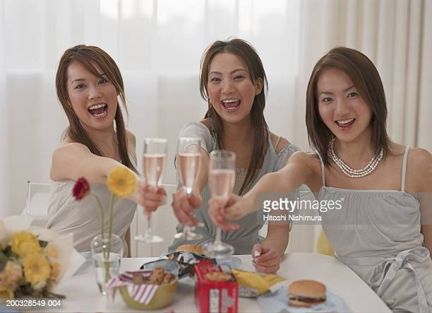 Three young women toasting champagne, smiling, portrait