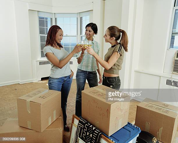 Three young women toasting drinks in apartment