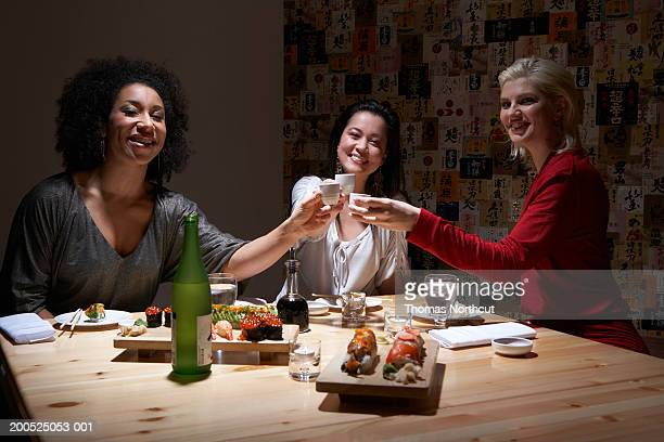 Three young women toasting with sake in sushi bar, portrait