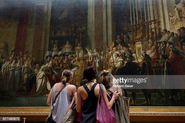 Three young women tourists admire The Coronation of Napoleon a painting of almost 10 x 6 metres completed in 1807 by JacquesLouis David the official...