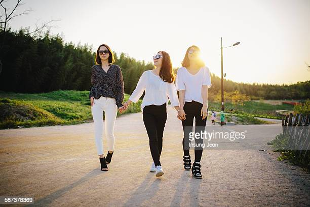 Three young women walking in park