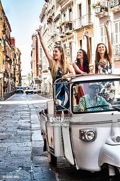 Three young women waving from open back seat of Italian taxi, Cagliari, Sardinia, Italy