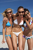 Three young women wearing bikinis standing together on beach, smiling