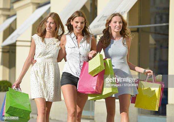 Three young women with colorful shopping bags