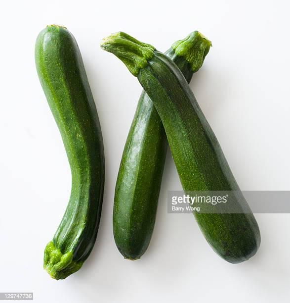 Three zucchini on white