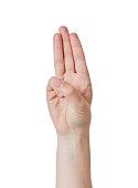 A raised hand gives a three-fingered salute, used by the Scouts, in the Hunger Games movie series and as a symbol of the Holy Trinity.
