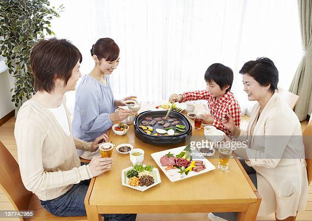 Three-generation family eating Japanese barbeque